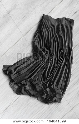 Black chiffon pleated skirt lying on white wooden background