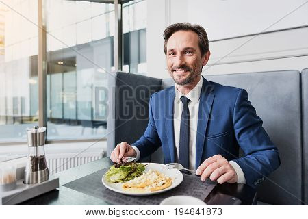 This dish is wonderful. Portrait of excited businessman eating omelet in restaurant and smiling. He is looking at camera with happiness
