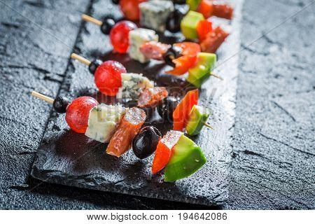 Various Finger Food With Fresh Ingredients On Black Rock