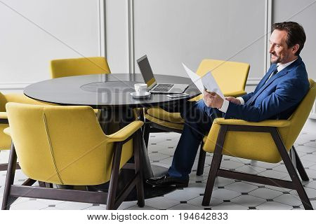 Wonderful result of works. Cheerful businessman is reading documents with satisfaction and smiling. He is sitting at round desk with notebook and cup of coffee