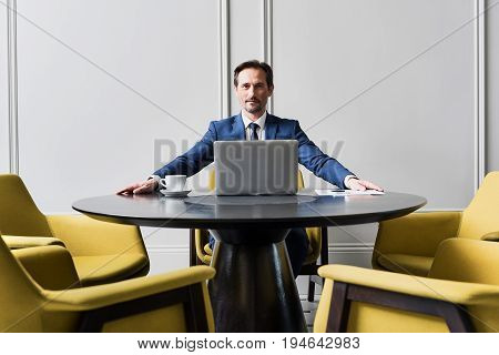 Portrait of successful businessman sitting at round table for negotiations. He is looking forward seriously. Laptop and documents are workplace