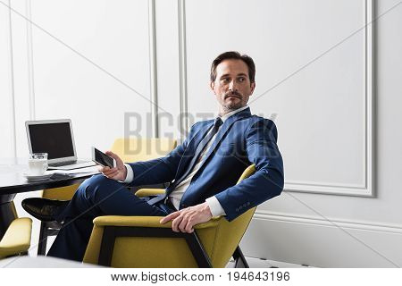 Portrait of mistrustful senior male manager looking back pensively while working in his office. He is holding smartphone. Copy space in right side
