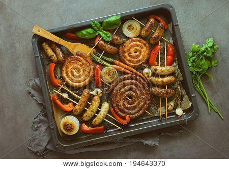 Beef and turkey herbed spicy sausages roasted on an oven sheet pan and garnished with roasted paprica onions and carrots view from above