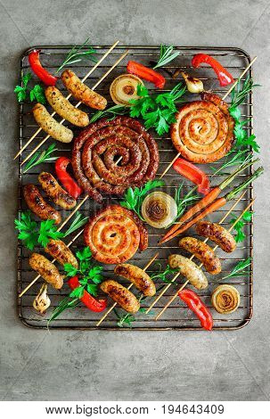 Roasted assorted sausages garnished with fresh greens and roasted paprika on an oven grill view from above