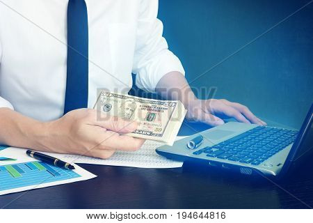 Online loan concept. Manager is holding money in a hand and laptop.
