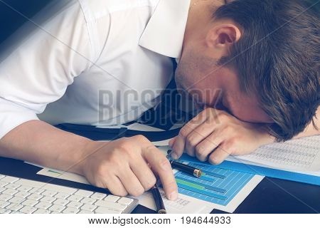 Chronic fatigue syndrome concept. Overworked businessman is sleeping at desk.