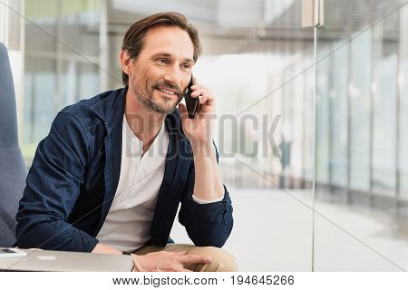 Portrait of cheerful middle-aged man telling something to his interlocutor by the phone. He is sitting near glass wall and smiling. Copy space