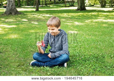 Child playing with spinner while sitting on the grass