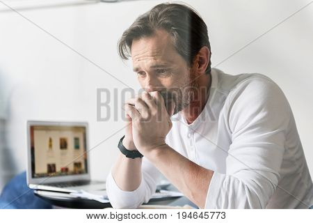 Portrait of disparate businessman is crying because of bankruptcy. He is sitting near open laptop
