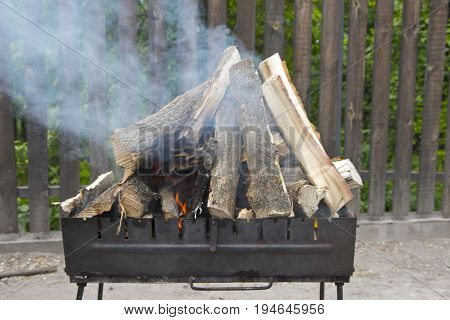 Ignition of firewood outdoors. preparing firewood for cooking barbecue. fry meat on the grill.