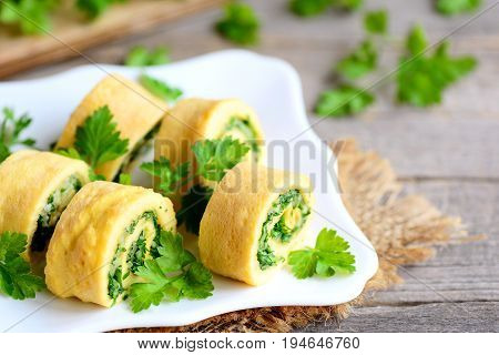 Eggs omelet rolls with cheese and greens on a plate and a vintage wooden table. Delicious stuffed omelet appetizer. Country style