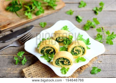 Eggs omelette rolls with cheese and greens on a plate, fork and knife on a vintage wooden table. Tasty stuffed omelette recipe. Rustic style