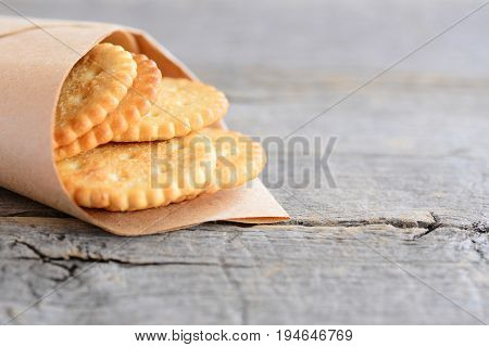 Dry wheat cookies in a wrapping paper and an old wooden background with empty copy space for text. Salty crackers cookies idea for kids or adults. Rustic style