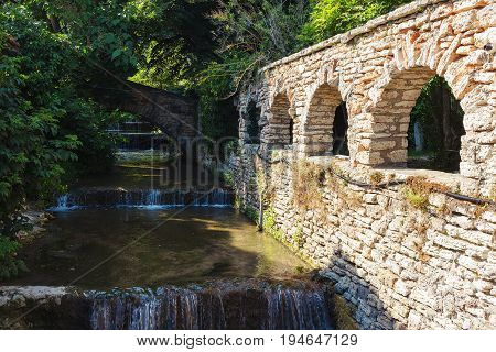 Old and antic stone wall water channel cascade.