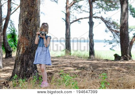 A little girl with a retro camera takes pictures in the forest a copy of the free space. A small photographer a rest and a hobby.