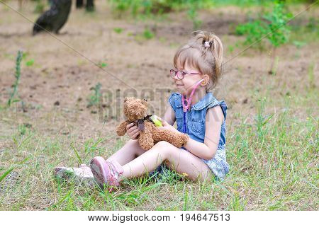 A little girl treats her teddy bear in a forest glade a copy of the free space. Summer vacation in nature.