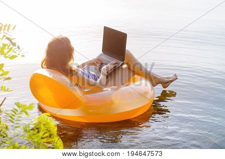 Young Woman Working On A Laptop In The Water On An Inflatable Ring, Copy Space For Your Text. Work O