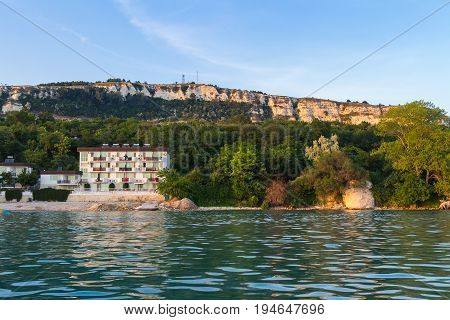 View of the buildings and big rock hills in Balchik city on black sea coast in Bulgaria at gold sunset time.