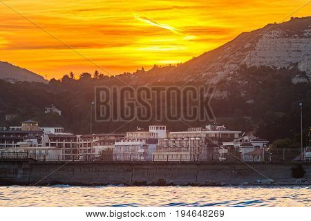 Golden sunset scenery on Black sea coast view on big hills and buildings in Balchik city Bulgaria.