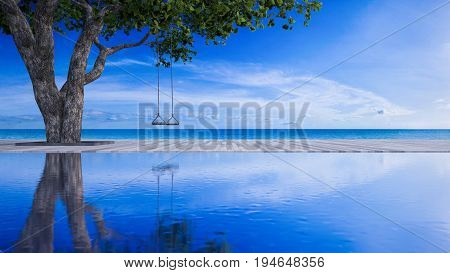3d rendering image of rope swing under the tree placed on timber deck and swimming pool which have blue sky and sea as background. sea view deck in day light.