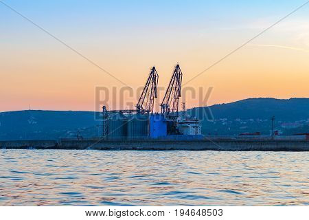 View of the sea port terminal with cranes at sunset time in Balchik Bulgaria.