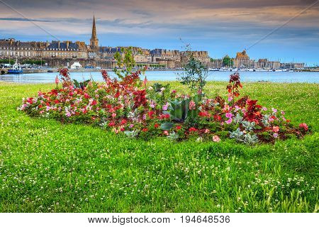 Spectacular walled city and luxury yacht harbor with blossoming colorful flowerbeds in summer city park Saint Malo Brittany region France Europe