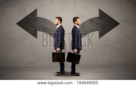 Young conflicted businessman choosing between two directions represented by black arrows