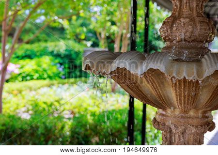 Garden with small fountain and benches around Fountain of water drops