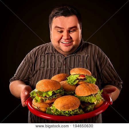 Fat man eating fast food hamberger and carries treat for friends on tray. Breakfast for overweight person. Junk meal leads to obesity.