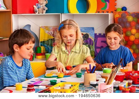Small students painting in art school class. Child drawing by paints on table. Boy and girls in kindergarten. Best children's club with happy and clever kids.
