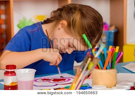 Small student girl painting in art school class. Child drawing by paints in orphanage. Craft girl lean very low over table.