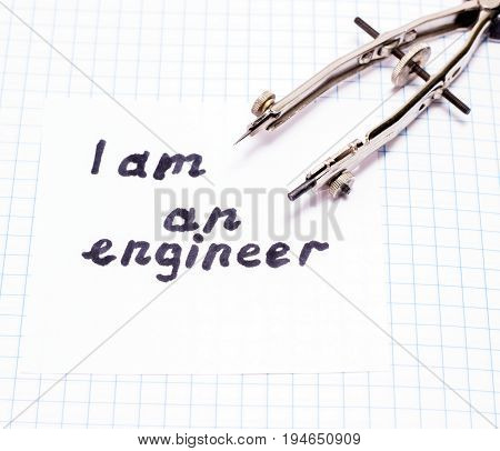 An inscription in English I am an engineer on a sheet of paper beside a compass is a necessary tool for drawing circles
