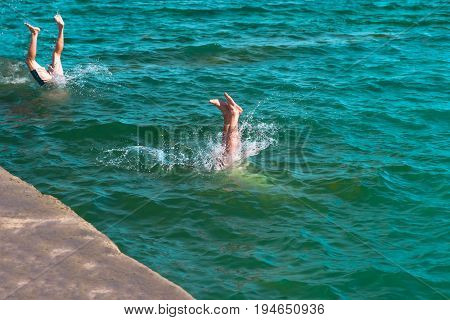 A young man's legs disappearing as he dives into the in a refreshing sea ocean On a hot summer day
