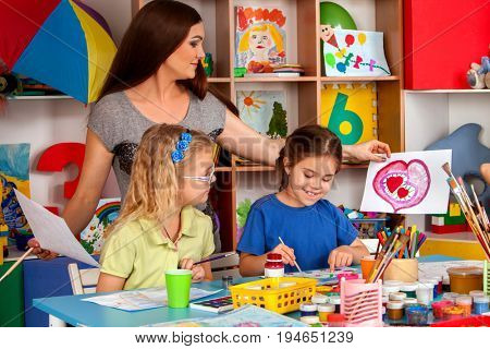 Craft lesson in primary school. Kindergarten teacher and small students work together. Girls at drawing lesson. Girl paints felt-tip pen picture in class. Children with teacher are preparing for an