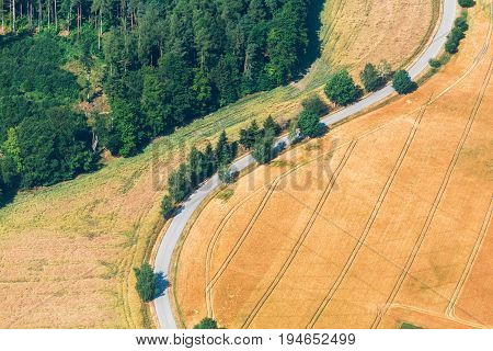 Aerial view of field road and trees from plane summer countryside