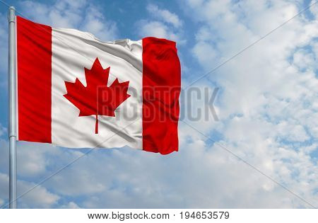 National flag of Canada on a flagpole in front of blue sky.