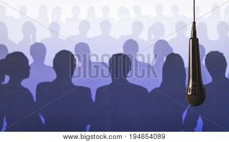 Public speaking and giving speech. Singing to mic in karaoke or talent show background. Microphone hanging from ceiling from wire in front of a crowd of silhouette people.