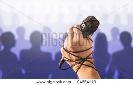 Stage fright in public speaking or bad karaoke singing live in front of crowd of people. Problem with speech or failed talent show performance. Microphone wire, cable and cord wrapped around hand.