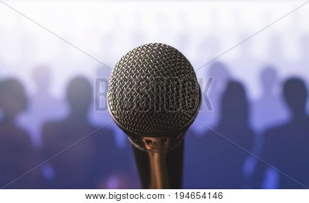 Close up of microphone in front of a silhouette audience and crowd of people. Public speaking and giving speech. Stage fright or training to talk. Singing to mic in karaoke or talent show concept.