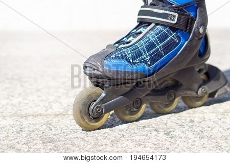 Close up to roller skate. Rollerskates and inline skates on tarmac and asphalt in the city.