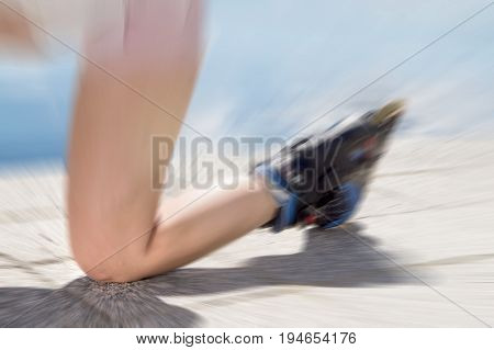 Young woman on roller skates falling down on ground, asphalt and road knee first. Inline and rollerskates accident. Painful injury to leg.