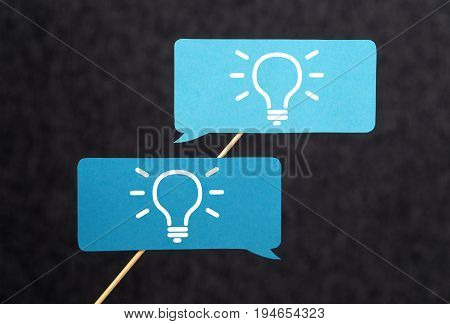 Innovation, brainstorm, inspiration and teamwork concept. Come up with new innovative and creative ideas together with the team. Cardboard speech bubbles on wooden stick with light bulb icons.