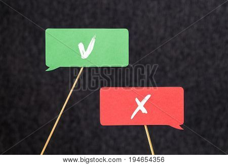 Right and wrong. Disagreement, argument and fight concept. Different opinions, morals and values. V and X sign on cardboard speech bubbles and chat balloons on wooden stick.