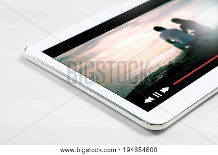 Online movie stream with mobile device. Close up to white tablet on wooden table with imaginary video player and film streaming service.