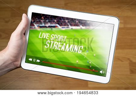 Man watching live sport stream online with mobile device. Hand holding tablet with imaginary video player and streaming service.