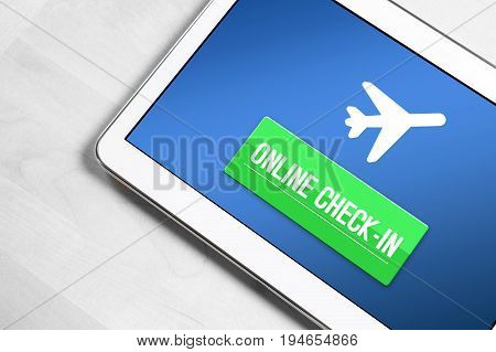 Online check in with tablet. Top view to mobile device on wooden table ready to checking in to flight on internet, web or application. Self service provided by airline.