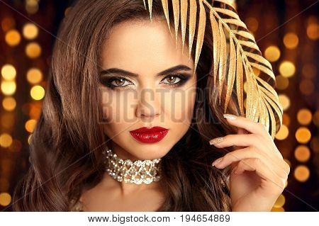 Beauty Fashion Brunette Portrait In Gold. Sexy Elegant Woman With Red Lips, Golden Eyeshadow Makeup