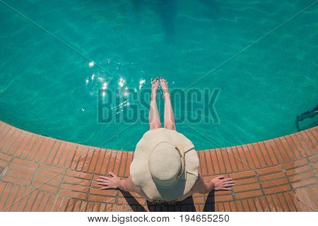 Top dow view of female at the poolside. Summer vacation concept. Space for copy.