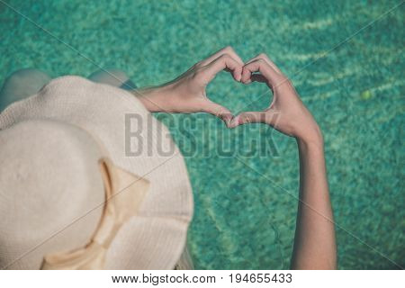 Top down view of female in hat showing heart shape wit her hands. Love and summertime concepts.