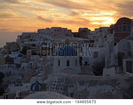 White and blue Greek Island Style architecture against golden evening sky at Oia village, Santorini Island, Greece